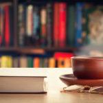 Книга, очки и чайная чашка на столе