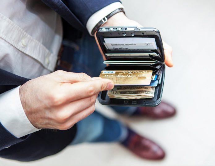 Мужчина кладет карту в бумажник