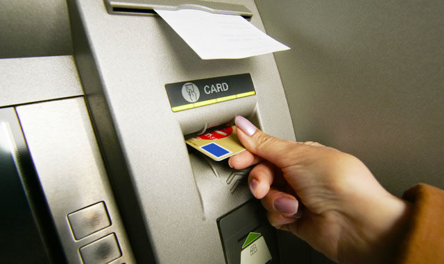 Женщина вставляет карту в банкомат