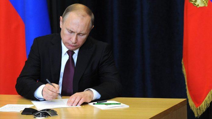 Владимир Путин подписывает документы